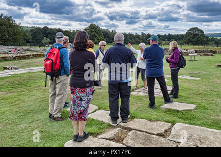 11 August 2018: Northumberland, UK - Visitors listening to a guide on a tour at Chesters Roman Fort, Hadrian's Wall, Northumberland, UK - Stock Image
