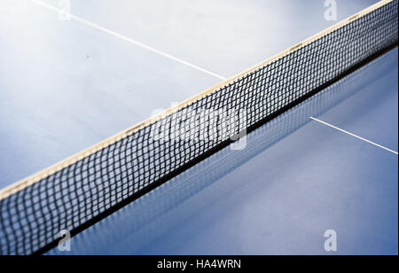 Diagonal table tennis net on a blue tabletennis table. Copy space area for sport themed designs and backgrounds - Stock Image