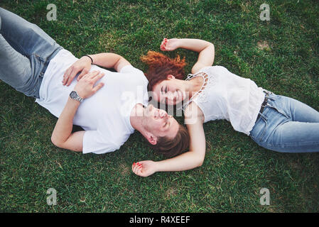 A romantic couple of young people lying on the grass in the park. Top view - Stock Image