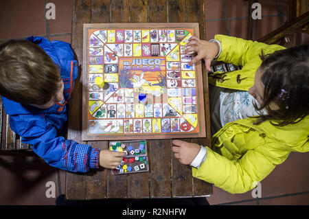 Little brothers playing Game of the Goose over wooden vintage table. Overhead view. Traditional board game - Stock Image