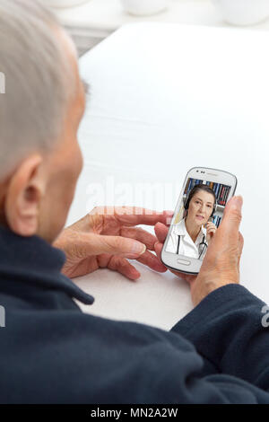 Senior person sitting with her smartphone at a table having a video call with her doctor, modern lifestyle concept - Stock Image