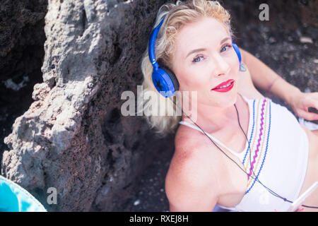 Pretty middle age young woman looking at smiling at the camera while listen music with blue headphones with star - red lipstick and blue eyes caucasia - Stock Image