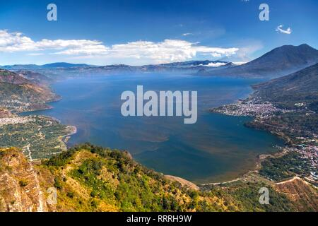 Aerial Landscape View of Blue Lake Atitlan surrounded by volcanoes in Guatemala Highlands with distant Panajachel and San Pedro Villages on Horizon - Stock Image