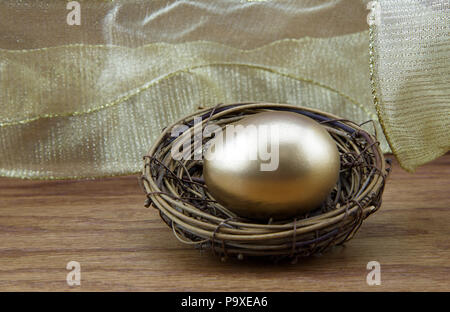 Secure nest egg concept reflected in gold tones and wood grain background - Stock Image