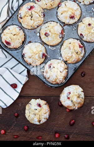 Cranberry Muffins  in a muffin tin with kitchen towel over a rustic wood  background with scattered fresh cranberries on the table. - Stock Image