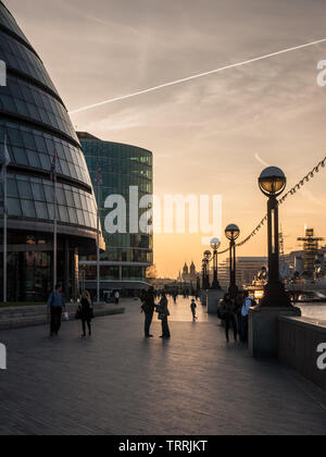 London, England, UK - April 23, 2010: People walk along the River Thames Path outside London City Hall at sunset. - Stock Image