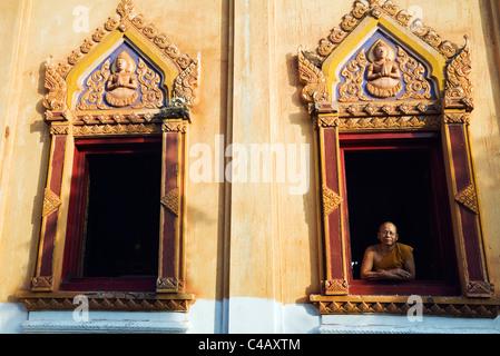 Thailand, Nong Khai, Nong Khai. A monk looks out from a window at Wat Hai Sok. - Stock Image