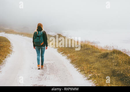 Tourist woman walking alone outdoor Travel Lifestyle wanderlust concept foggy nature adventure active vacations - Stock Image
