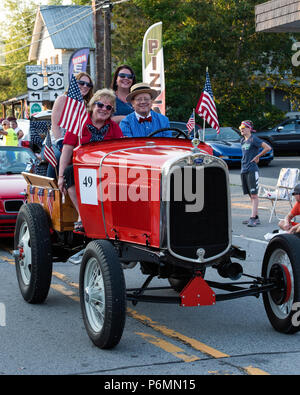 A fancy orange 1931 Ford Model A Doodlebug Tractor driving in the 4th of July Parade in Speculator, NY USA - Stock Image