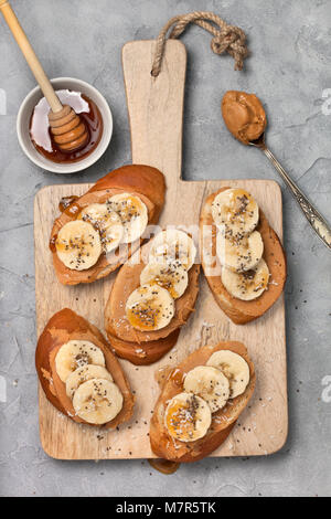 healthy breakfast. sandwich with peanut butter, banana, honey, chia seeds and coconut sprinkled on a gray concrete - Stock Image