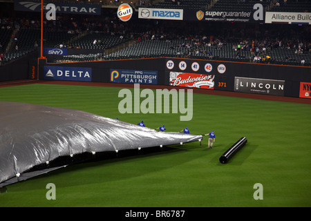 Citi Field grounds crew pulling the tarp on the field after a rain delay, Queens, NY, USA - Stock Image