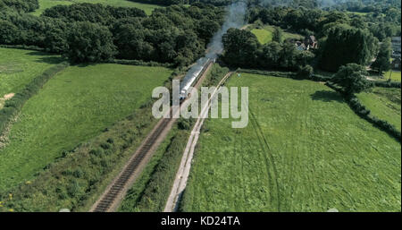 Aerial view of an old fashioned steam train crossing the English countryside - Stock Image