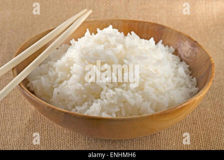 Jasmine rice in a handmade wooden bowl and chopsticks. - Stock Image