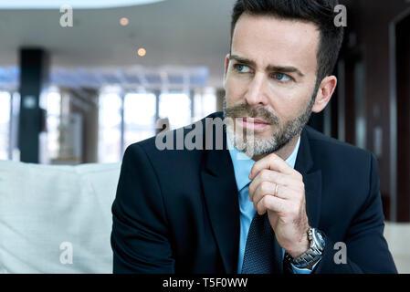 Thoughtful businessman sitting on sofa - Stock Image