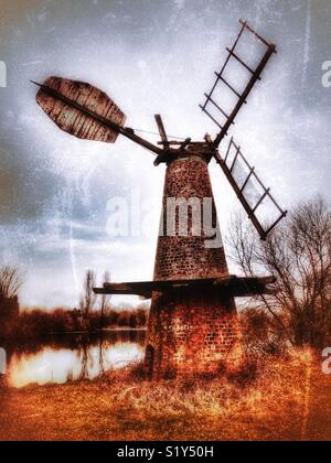 Disused windmill beside a pond, near Howden, East Yorkshire, England, UK - Stock Image