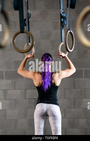 Rear view of a fit strong woman holding the rings in a gym showing her muscular physique as she prepares to work out in a health and fitness concept - Stock Image