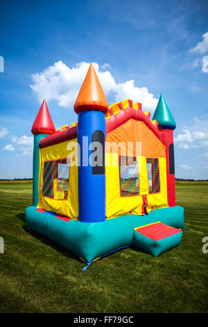 Children's bouncy house castle in a large open yard. - Stock Image