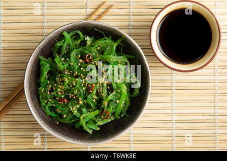 Wakame seaweed salad with sesame seeds and chili pepper in a bowl on a bamboo mat - Stock Image