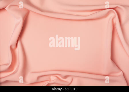 background of peach fabric draping close-up - Stock Image