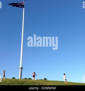 Girls playing on hill with Australian flag in Canberra - Stock Image