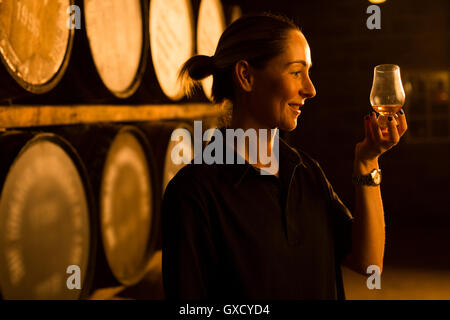 Female taster looking at the colour of whisky in glass at whisky distillery - Stock Image