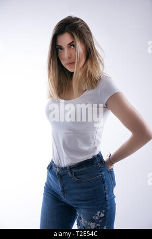 Beautiful brown haired girl in a white t shirt and blue jeans and hands in ass pockets on a white background in studio. Woman portrait and fashion - Stock Image