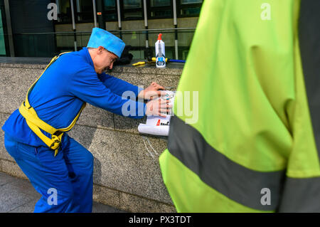 London, UK. October 19th, 2018. A security man approaches to take poster and past as 'Commander Neil Godwin Tracy' of International Rescue puts a poster on the wall of  the Dept for Business, Energy and Industrial Strategy (BEIS) after he had been refused entry. He had come to offer his organisation's assistance, to produce policies which which recognise the desperate need to cut carbon emissions to avoid disastrous global warming and climate change by banning all fracking. Security staff at the ministry, which campaigners allege has spent more time on changing its name than developing sensibl - Stock Image
