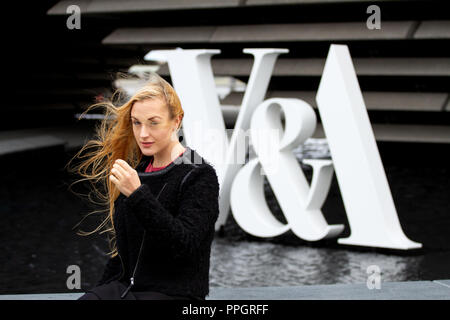 Dundee, Tayside, Scotland, UK. 25th September, 2018. UK weather: Strong winds with light rain sweeping across Tayside. A young blonde woman Rhianna Martin pays her first visit to the stunning new V&A building sitting outside the Museum entrance on a very windy day in Dundee, UK. Credits: Dundee Photographics / Alamy Live News - Stock Image