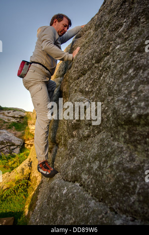 Rock Climber Jon Hawker bouldering at Tunhill Rocks on Dartmoor, a great bouldering location - Stock Image