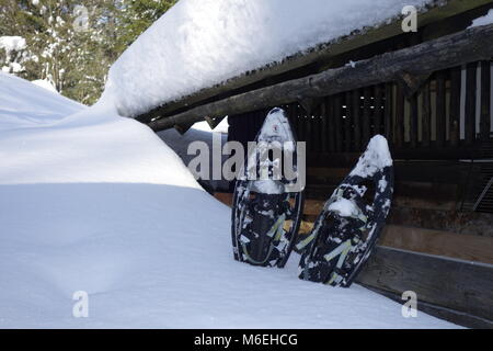 A pair of snow shoes stacked in the snow next to old woodshed. - Stock Image