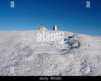 Snowy trig point on summit of Worm hill, near Tweedsmuir, Southern Uplands, Scotland - Stock Image