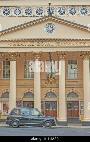 An iconic black London taxi passes the front of the Theatre Royal, Haymarket in London's theatreland - Stock Image