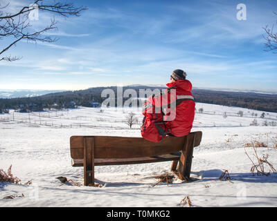 Man hiker with backpack in winter time walk around. Adventurer withj warm outdoor clothes, cap and sunglasses - Stock Image