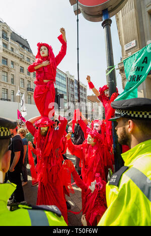 London, UK. 19th April 2019. Figures in red to represent the blood of extinct species outside the police cordon at Oxford Circus at Extinction Rebellion's Sea of Protest raise fists in support to those inside the cordon protecting the pink yacht Berta Cacares. Police were trying to persuade protesters to leave by threatening them with arrest and cutting off those who were locked on around the bottom of the yacht. There were a number of arrests of protesters who refused to leave. A few tried to get the large crowd to protect the yacht, but XR organisers persuaded them not to physically oppose t - Stock Image