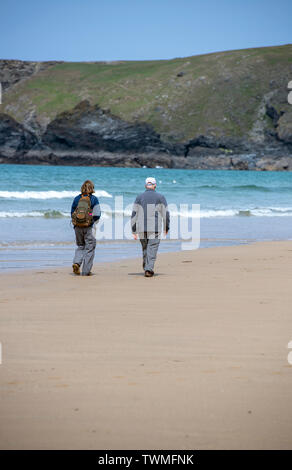 Elderly couple walking on the beach at Bedruthan Steps in Cornwall, England, UK - Stock Image