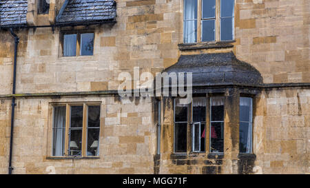 Cotswold limestone adorns the facade and ornate bay of this elegant terraced house in the picturesque market town high street of Chipping Campden - Stock Image
