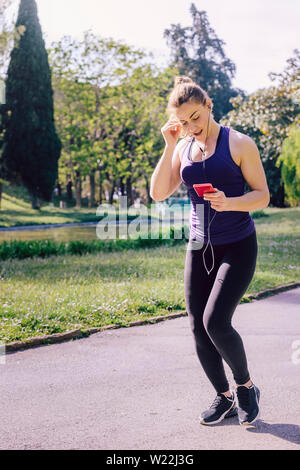 vertical photo of an attractive blonde sports woman putting on headphones while running outdoors at park, fitness accessories - Stock Image