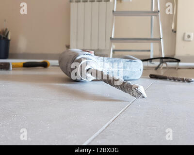 Electric hand drill and drill bits for concrete and different other tools on the floor - Stock Image