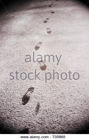A light dusting of snow with a pedestrians' footprints visible. - Stock Image