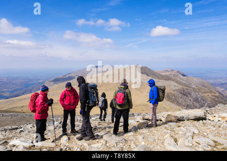 Hikers hiking down Glyder Fawr to Y Garn mountain in mountains of Snowdonia National Park. Ogwen, Gwynedd, Wales, UK, Britain - Stock Image