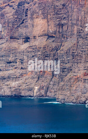 Sheer seacliffs of Los Gigantes  with seamed rugged rock faces meet the calm blue atlantic ocean on the west coast of Tenerife, Canary Islands, Spain - Stock Image