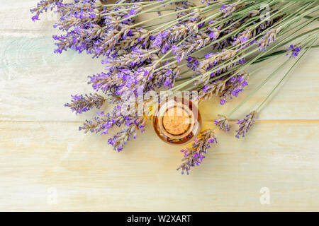 Lavender essential oil with lavender flowers on a rustic wooden background with copyspace, toned image. A glass bottle with buds infusing - Stock Image