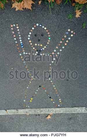 Street art - metal beer bottle tops impregnated in to the pavement to form a human shape, in Milan, Italy. - Stock Image