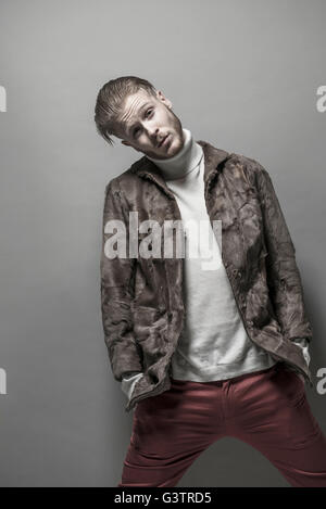 Studio portrait of a cool young man wearing a fur jacket. - Stock Image