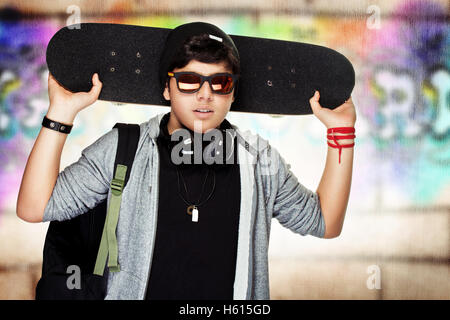 Stylish teen boy with skateboard, urban graffiti wall background, active handsome guy listening music, modern life - Stock Image