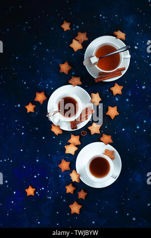 Teatime with star-shaped cookies. White porcelain cups on a starry sky background. Outer space and astronomy food photography. - Stock Image