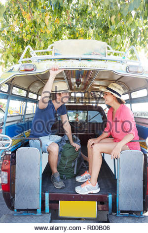 Young couple sitting in tour bus - Stock Image