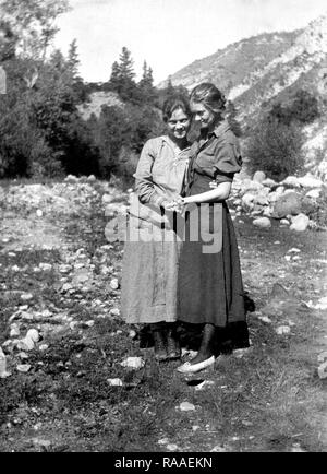 Two young women pose together holding hands in Colorado, ca. 1925. - Stock Image