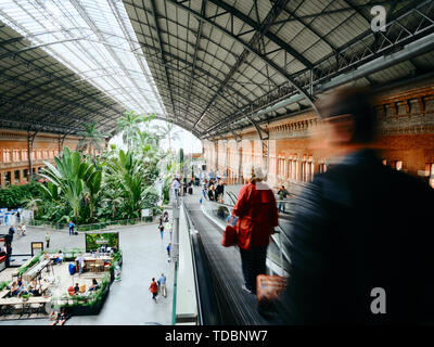People commuting and walking inside Atocha train station in Madrid - Stock Image