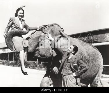 Young man looking at woman lifted by elephant - Stock Image